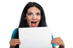 Überraschte Frau, die eine Leerseite anhält Lizenzfreies Stockfoto
