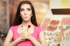 Überraschte Frau, die eine Make-upbürste hält Stockbilder