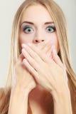 Überraschte Frau, die ihren Mund mit den Händen bedeckt Stockfotografie