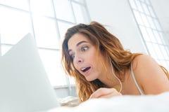 Überraschte Frau, die Laptop-Computer auf dem Bett verwendet Stockbild