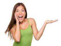 Überraschte Frau, die Produkt zeigt Stockfotos