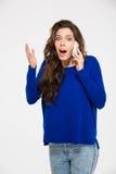 Überraschte Frau, die am Telefon spricht Stockfotografie