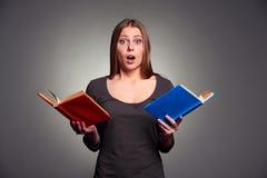 Überraschte Frau mit Büchern Stockfotos