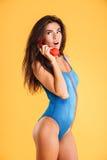 Überraschte gelockte Frau im blauen Badeanzug sprechend am roten Telefon Lizenzfreie Stockfotografie