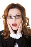 Überraschte Geschäftsfrau, die ihren Kopf hält Stockfotografie