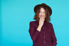 Überraschte junge Frau über blauem Türkishintergrund Stockfoto
