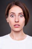 Überraschte junge Frau über dunklem Hintergrund Lizenzfreie Stockfotografie