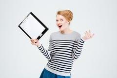 Überraschte junge Frau, die Klemmbrett hält Stockbilder