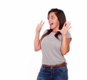 Überraschte junge Frau, die mit den Händen oben schreit Lizenzfreie Stockfotos