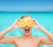 Überraschte junge Frau mit orange Scheiben Lizenzfreies Stockfoto