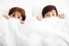 Überraschte junge Paare, die im Bett liegen Stockbild