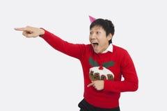 Überraschte Mann tragende Weihnachtsstrickjacke beim Zeigen über weißen Hintergrund Lizenzfreies Stockfoto