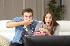 Überraschte Paare, die fernsehen Stockfotografie