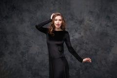 Überraschte recht junge Frau im schwarzen Kleid Stockbild