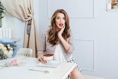 Überraschte schöne junge Frau, die im Café sitzt Lizenzfreie Stockbilder