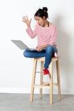 Überraschte schöne junge Frau, die mit Überraschung zu ihrem Computer sich verständigt Lizenzfreie Stockfotos