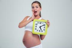 Überraschte schwangere Frau, die Wanduhr hält Stockfotografie