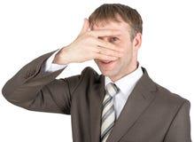 Überraschte versteckende Augen des jungen Mannes hinter seiner Hand Stockfoto