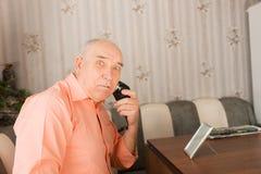 Überraschter alter Mann, der Bart an seinem Tisch rasiert Stockfoto
