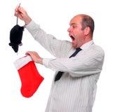 Überraschter Geschäftsmann mit ungewöhnlicher Weihnachtsgratifikation. Stockbilder