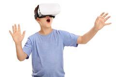 Überraschter Junge, der in ein VR-Schutzbrillen schaut Stockfotos