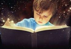 Überraschter Junge mit magischem Buch Stockfotografie