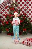 Überraschter Junge mit Weihnachtsgeschenk Lizenzfreie Stockfotos