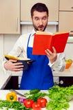 Überraschter junger Mann mit Kochbuch Stockbild
