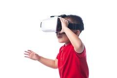 Überraschter kleiner asiatischer Junge, der in ein VR-Schutzbrillen schaut und wi gestikuliert Stockfotos