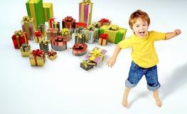 Überraschter kleiner Junge mit vielen Geschenken Stockbild