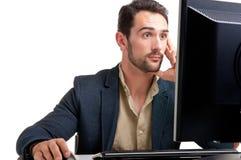 Überraschter Mann, der einen Computer-Monitor betrachtet Stockbilder