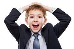 Überraschter oder überraschter Kinderjunge im Anzug, der an Haare hält Stockfotos