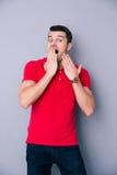 Überraschter zufälliger Mann, der seinen Mund bedeckt Stockfoto