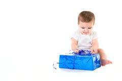 Überraschtes Baby mit Geschenk Stockbild
