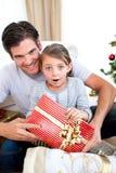 Überraschtes kleines Mädchen, das ein Weihnachtsgeschenk anhält Lizenzfreie Stockfotografie