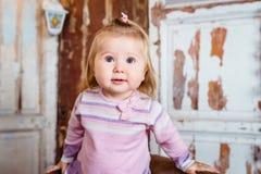 Überraschtes lustiges blondes kleines Mädchen mit großen grauen Augen Stockfotos