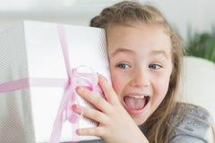 Überraschtes Mädchen, das ein Geschenk rüttelt Lizenzfreie Stockfotografie