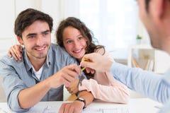 Überreichende Schlüssel der Immobilien zu den Paaren Stockfotografie