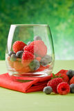 Berries. Photo of delicious berries inside a crystal glass in front of green background Stock Photo