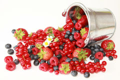 Berries. Strawberries, red currants, raspberries and blueberries on white falling out of a bucket stock photo