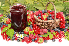 Berries. Strawberries, red currants, raspberries and blueberries on white with a basket and a marmalade jar stock image