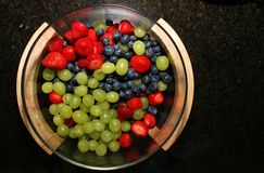 Berries from above. A bowl of fresh berries, strawberries, blueberries, grapes shot from straight above Stock Images