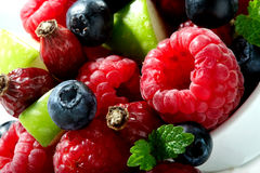 Berries, apple pieces and mint leaves close-up on white Stock Images