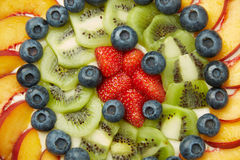 Berries, Apples and Kiwis on Top of Tasty Cake. High Angle Shot of Fresh Blueberries, Strawberries, Apples and Kiwis on Top of a Delicious Cake stock photo
