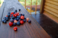 Berries on the balcony. Fresh forest berries on the wooden balcony outdoors Royalty Free Stock Images