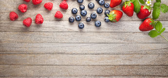 Berries Banner Wood Background. Various fresh berries, strawberries, raspberries and blueberries along the top edge of a rustic wood background Stock Photography