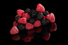 Berries on black. Delicious ripe raspberries and blackberries pile on black background. Luxurious healthy summer fruits stock photo