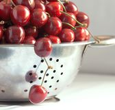 Berries of black cherries in a colander, two berries hang Stock Images