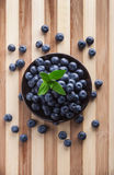 Berries in black jar. On wooden table Stock Images