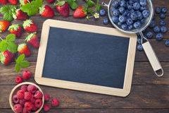 Berries Blackboard Chalkboard Sign Background. Various fresh berries, strawberries, raspberries and blueberries around the edge of a blank chalkboard sign on a Royalty Free Stock Photo